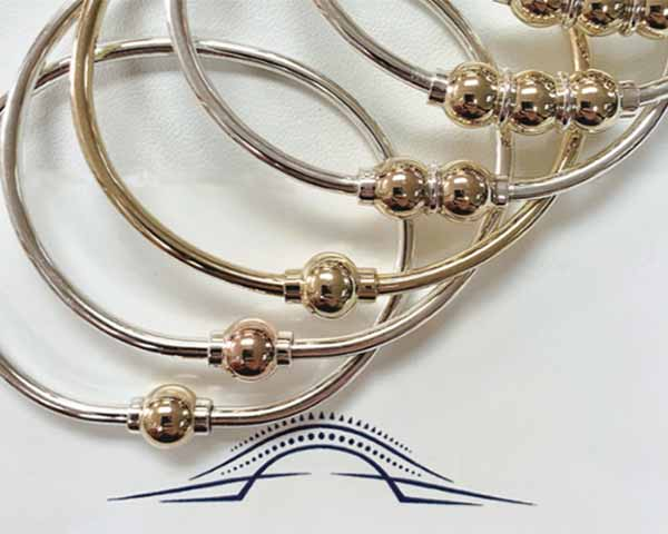 A stack of six Cape Cod bracelets with different configurations including classic one ball, two ball and three balls.
